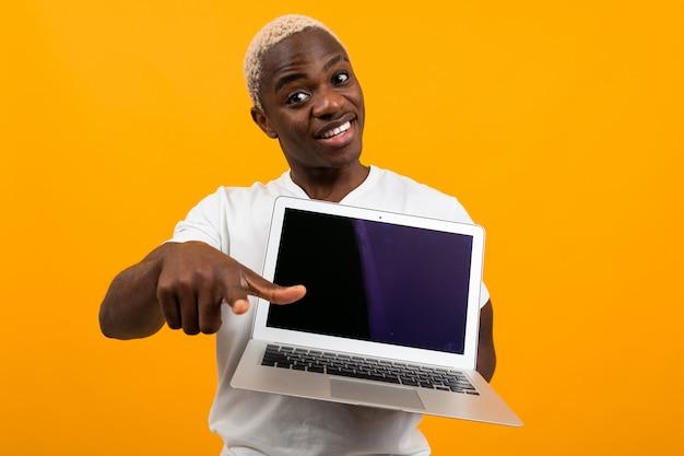 Sonriendo lindo estadounidense con cabello blanco en una camiseta blanca muestra una pantalla de computadora portátil con una maqueta y señala con el dedo hacia adelante en un estudio naranja