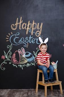 Sonriendo lindo niño pequeño con orejas de conejo de pascua
