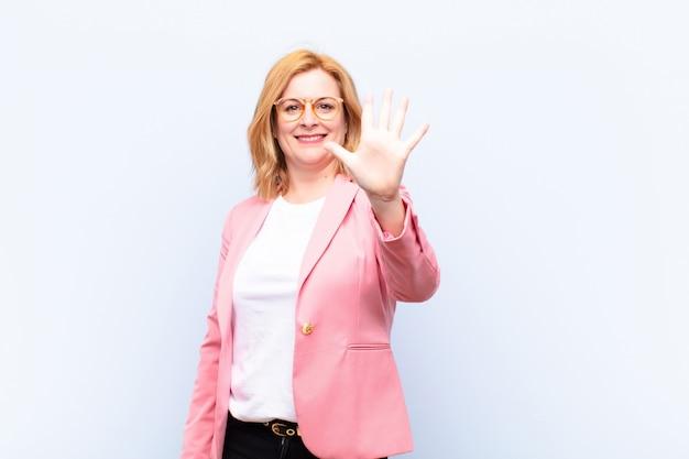 Sonriendo y luciendo amigable, mostrando el número cinco o quinto con la mano hacia adelante, contando hacia atrás
