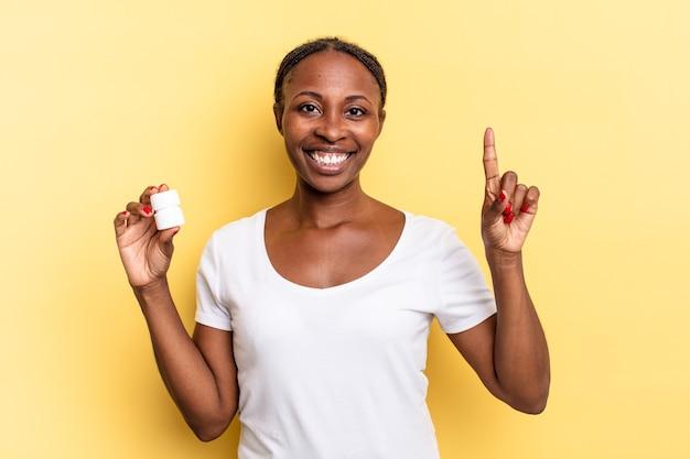Sonriendo y luciendo amigable, mostrando el número uno o el primero con la mano hacia adelante, contando hacia atrás. concepto de pastillas
