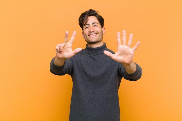 Sonriendo y luciendo amigable, mostrando el número ocho u octavo con la mano hacia adelante, contando hacia atrás