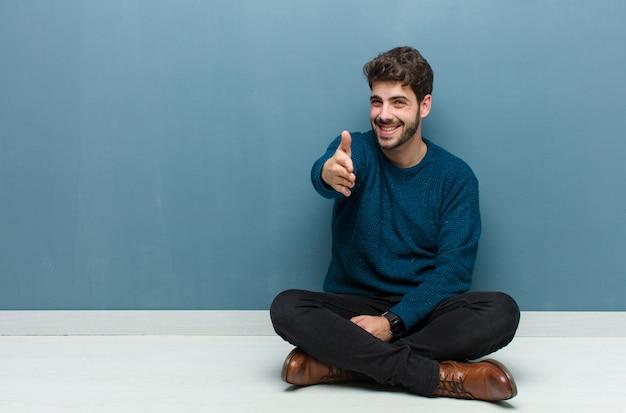 Sonriendo, luciendo feliz, confiado y amigable, ofreciendo un apretón de manos para cerrar un trato, cooperando