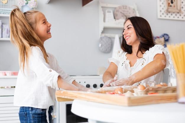 Sonriendo madre e hija cocinando