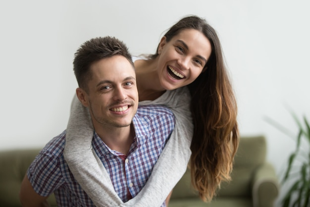 Sonriendo marido piggybacking alegre esposa en casa, feliz pareja retrato