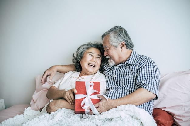 Sonriendo marido senior haciendo sorpresa dando caja de regalo a su esposa en el dormitorio