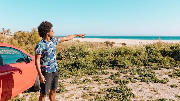 Sonriendo masculino étnico joven permanente por la orilla del mar y mostrando la dirección