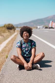 Sonriendo masculino étnico sentado en el camino