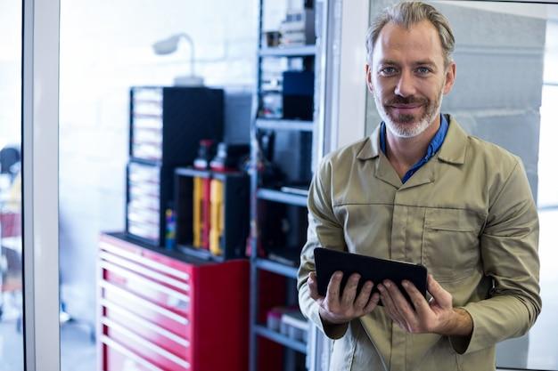 Sonriendo mecánico sosteniendo tableta digital