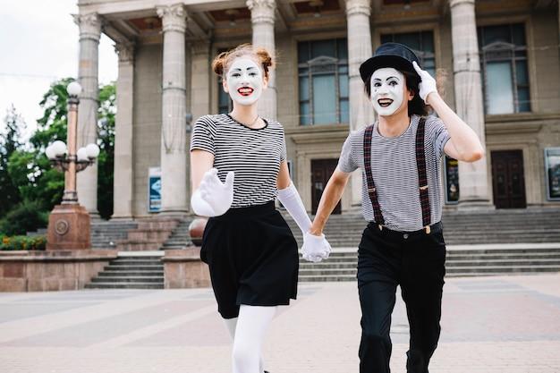 Sonriendo mime pareja corriendo frente al edificio
