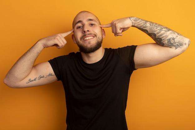 Sonriendo mirando hacia adelante chico guapo joven con camisa negra poniendo el dedo en la sien aislado en naranja