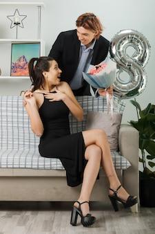 Sonriendo mirando el uno al otro joven pareja en feliz día de la mujer chico sosteniendo ramo de pie detrás en el sofá con la niña en la sala de estar