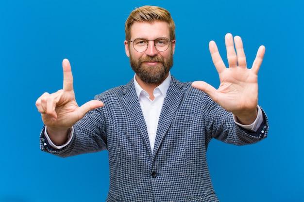 Sonriendo y mirando amigable mostrando el número siete o séptimo con la mano hacia atrás