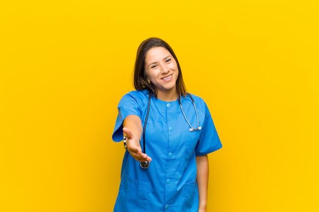 Sonriendo mirando feliz confiado y amigable ofreciendo un apretón de manos para cerrar un trato cooperando aislado contra la pared amarilla