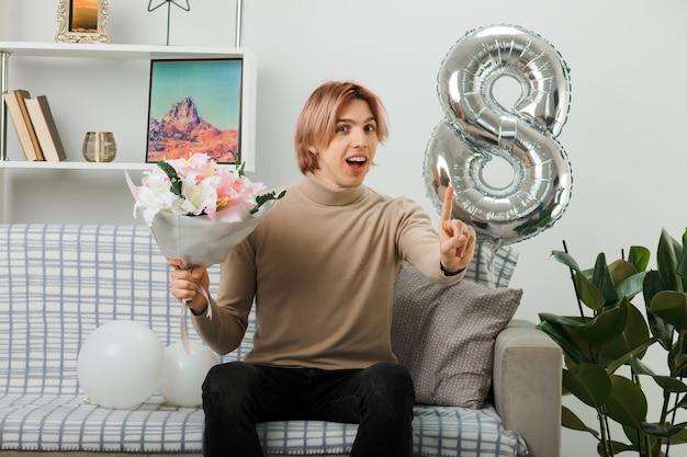 Sonriendo mostrando a un chico guapo en el día de la mujer feliz con ramo sentado en el sofá en la sala de estar