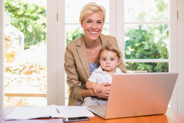 Sonriendo de mujer bonita rubia con su hijo usando laptop