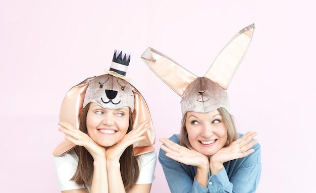 Sonriendo a mujeres bastante jóvenes con orejas de conejo y mirando el uno al otro sobre fondo rosa claro
