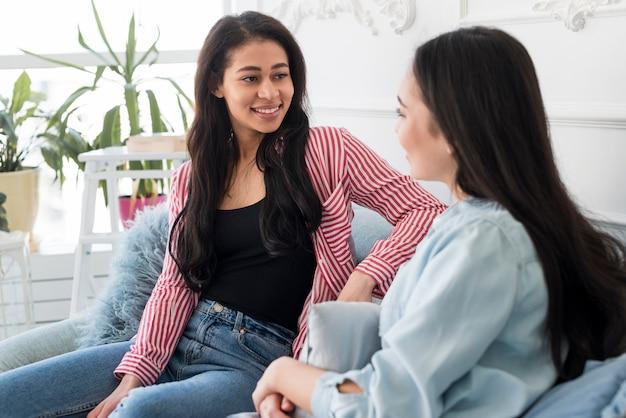 Sonriendo las mujeres jóvenes se comunican en casa