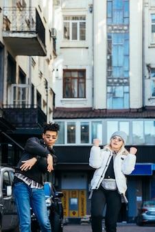 Sonriendo multi étnica joven pareja de pie debajo del edificio bailando en la calle
