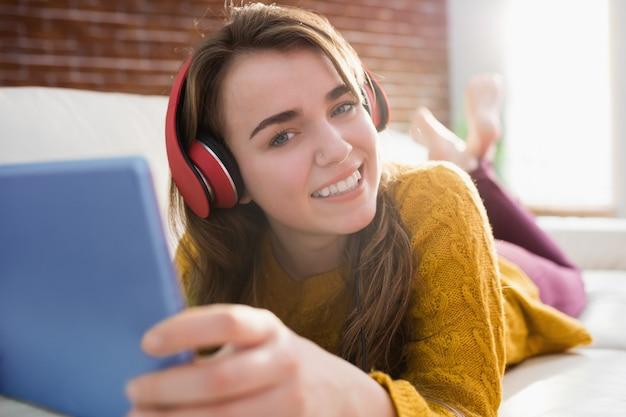 Sonriendo música que escucha de la mujer bonita con su tableta que miente en el sofá en la sala de estar