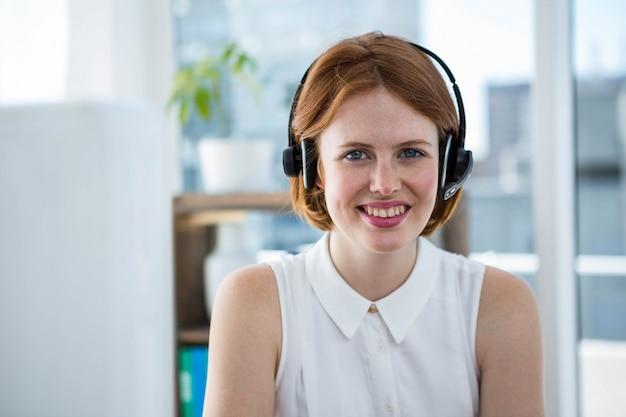 Sonriendo negocios hipster sentado en el escritorio con los auriculares puestos