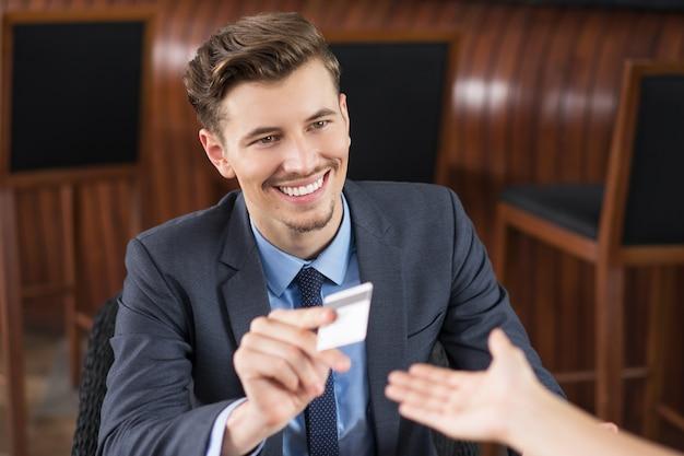 Sonriendo de negocios que da la tarjeta al camarero en el café