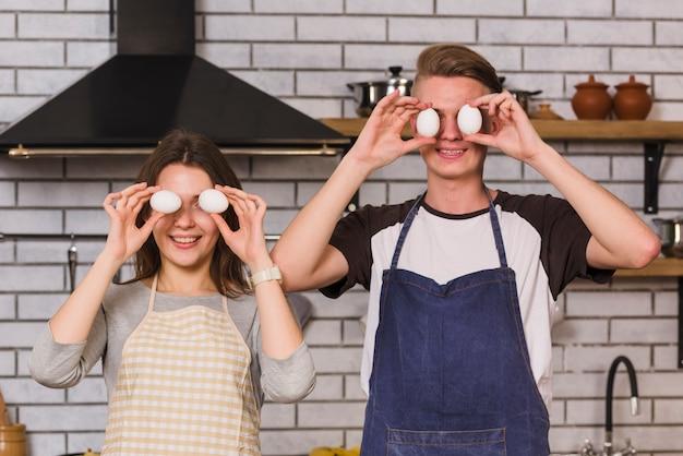 Sonriendo novios jugando con huevos en la cocina