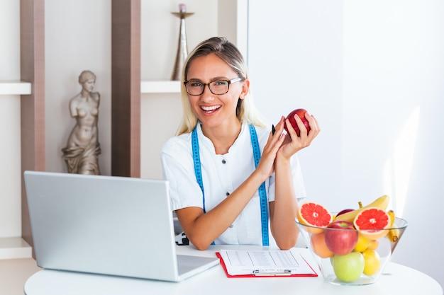 Sonriendo nutricionista en oficina sosteniendo una fruta