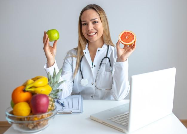 Sonriendo nutricionista en su oficina, muestra frutas saludables
