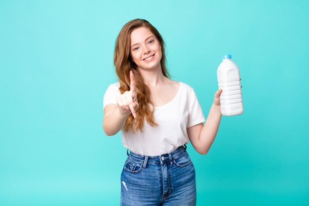 Sonriendo con orgullo y confianza haciendo el número uno y sosteniendo una botella de leche