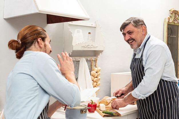 Sonriendo padre e hijo cocinando y mirándose