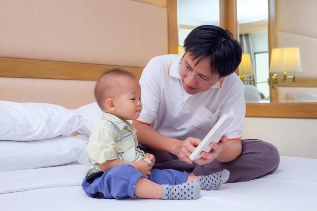 Sonriendo padre y su hijo leyendo libro de cuentos antes de acostarse