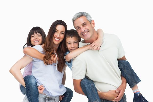 Sonriendo padres sosteniendo a sus hijos en la espalda