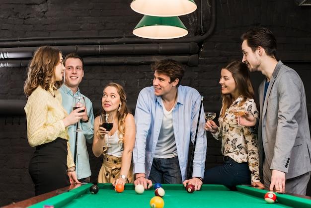 Sonriendo parejas en el club disfrutando de billar y bebidas