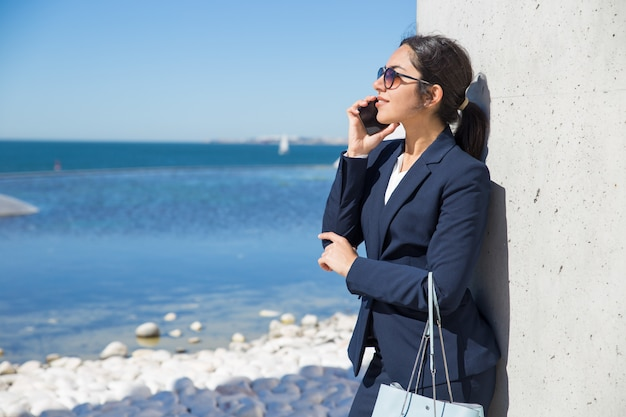 Sonriendo pensativa empresaria de pie por mar