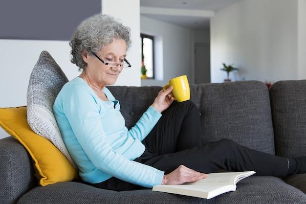 Sonriendo positiva jubilada señora emocionada con novela interesante