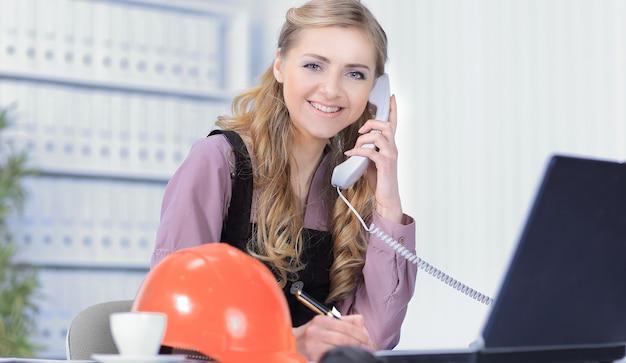 Sonriendo profesional hablando por teléfono en la oficina del arquitecto