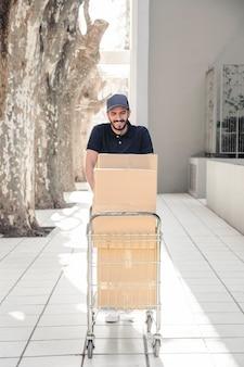 Sonriendo repartidor caminando sobre el pavimento con carro lleno de cajas de cartón