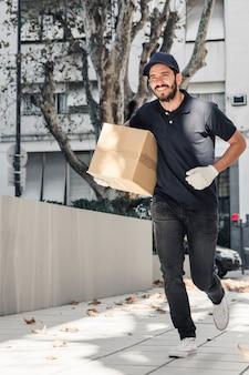 Sonriendo repartidor corriendo sobre el pavimento con paquete