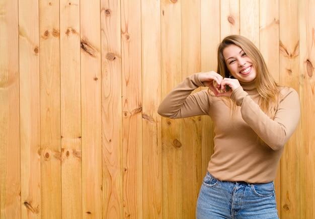 Sonriendo y sintiéndose feliz, lindo, romántico y enamorado, haciendo forma de corazón con ambas manos