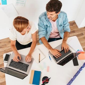 Sonriendo trabajando masculino y femenino sentado en el lugar de trabajo y usando computadoras portátiles mirando el uno al otro