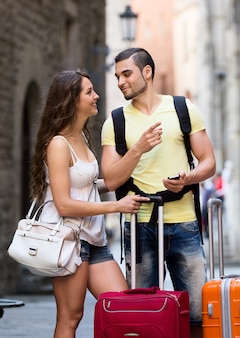 Sonriendo viajeros jóvenes buscando camino con teléfono