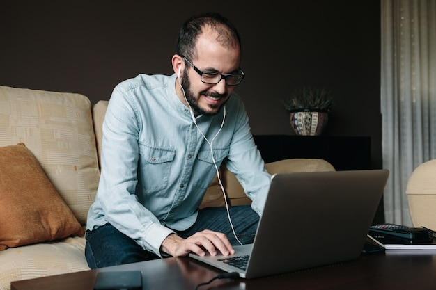 Sonriendo videoconferencia de hombre con compañeros de trabajo mientras trabaja remotamente desde casa