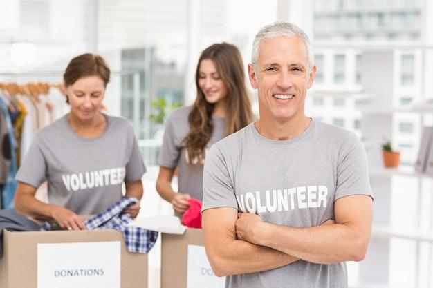 Sonriendo voluntario con los brazos cruzados
