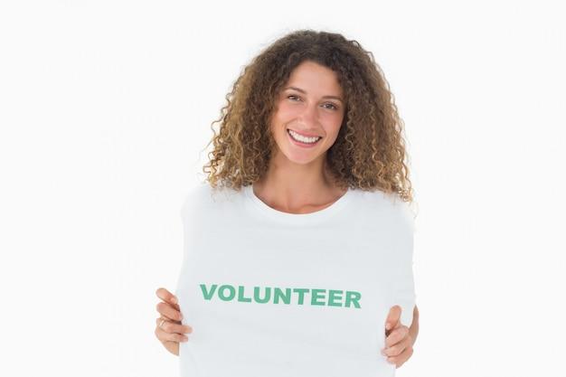 Sonriendo voluntario mostrando su camiseta a la cámara