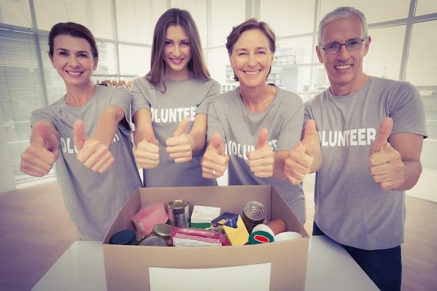 Sonriendo voluntarios haciendo pulgares arriba