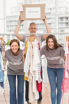 Sonriendo voluntarios de pie entre la ropa colgada