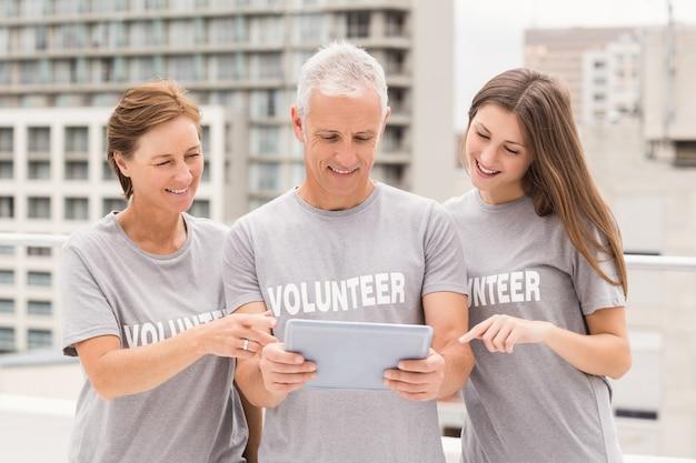 Sonriendo voluntarios usando tableta juntos