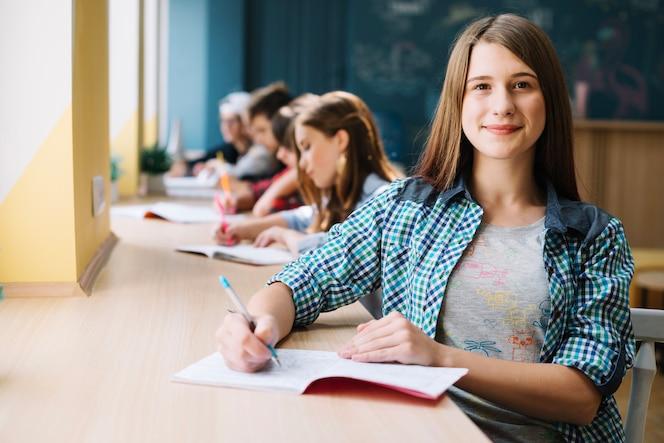 Sonriente adolescentes en el escritorio