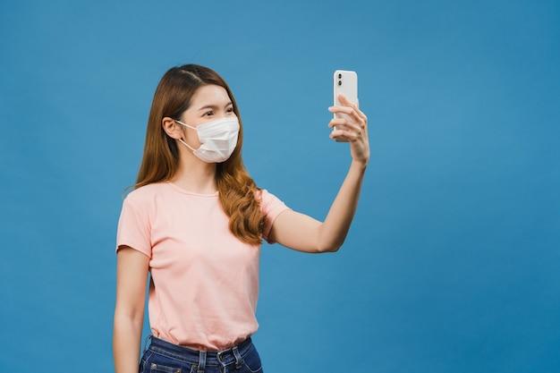 Sonriente adorable mujer asiática con mascarilla médica haciendo foto selfie en teléfono inteligente con expresión positiva en ropa casual y soporte aislado en la pared azul