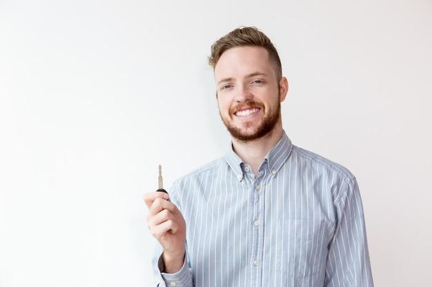 Sonriente agente de bienes raíces joven mostrando coche o llave de la casa